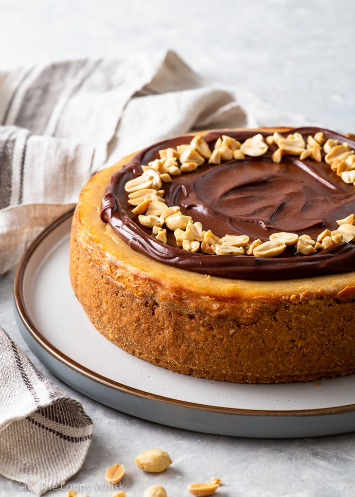Chocolate peanut butter cheesecake on a round serving plate, decorated with glossy chocolate ganache and chopped peanuts.