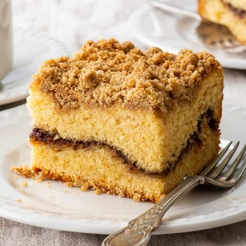 A piece of gluten free coffee crumb cake on a white dessert plate.