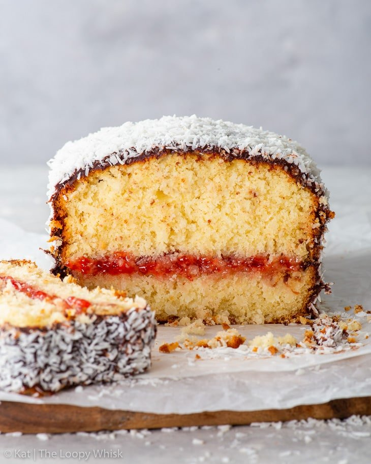 The cross-section of the lamington loaf cake, showing the delicate sponge and layer of jam in the middle.
