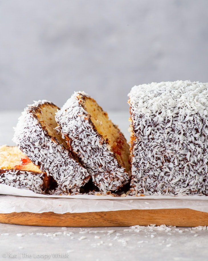 Side-on view of the lamington loaf cake with three pieces already cut.