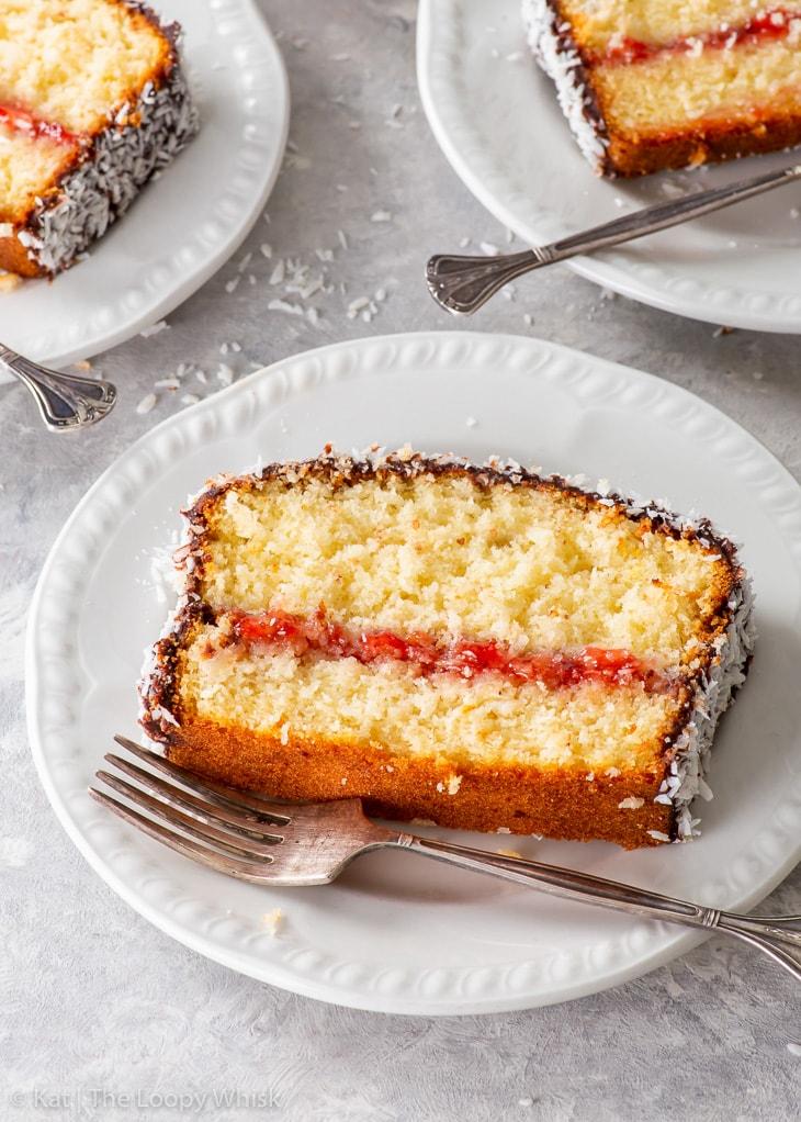 Three slice of laminton loaf cake on white dessert plates.