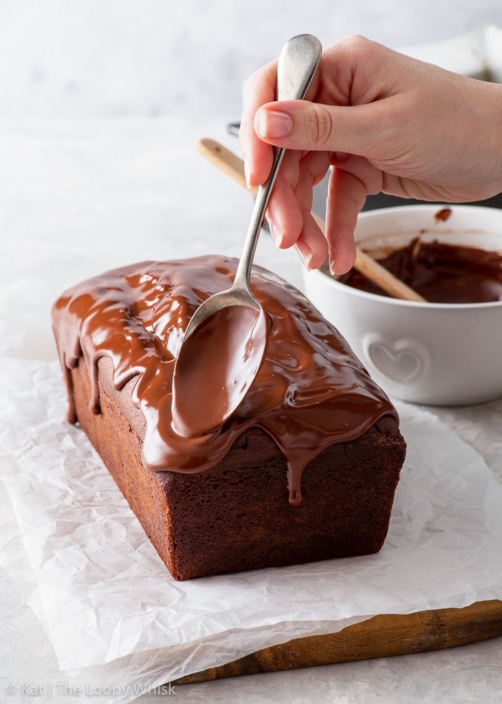 Spreading chocolate ganache glaze on top of the chocolate loaf cake.