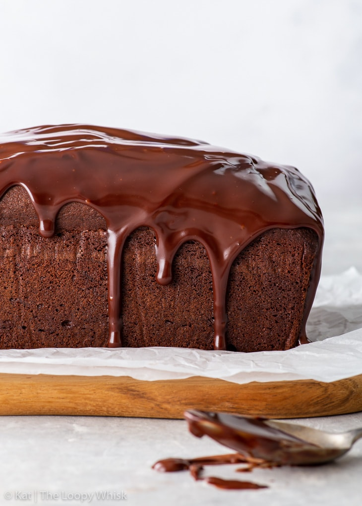 Side-on view of the chocolate loaf cake, drizzled with a chocolate ganache glaze, on a piece of white parchment paper.