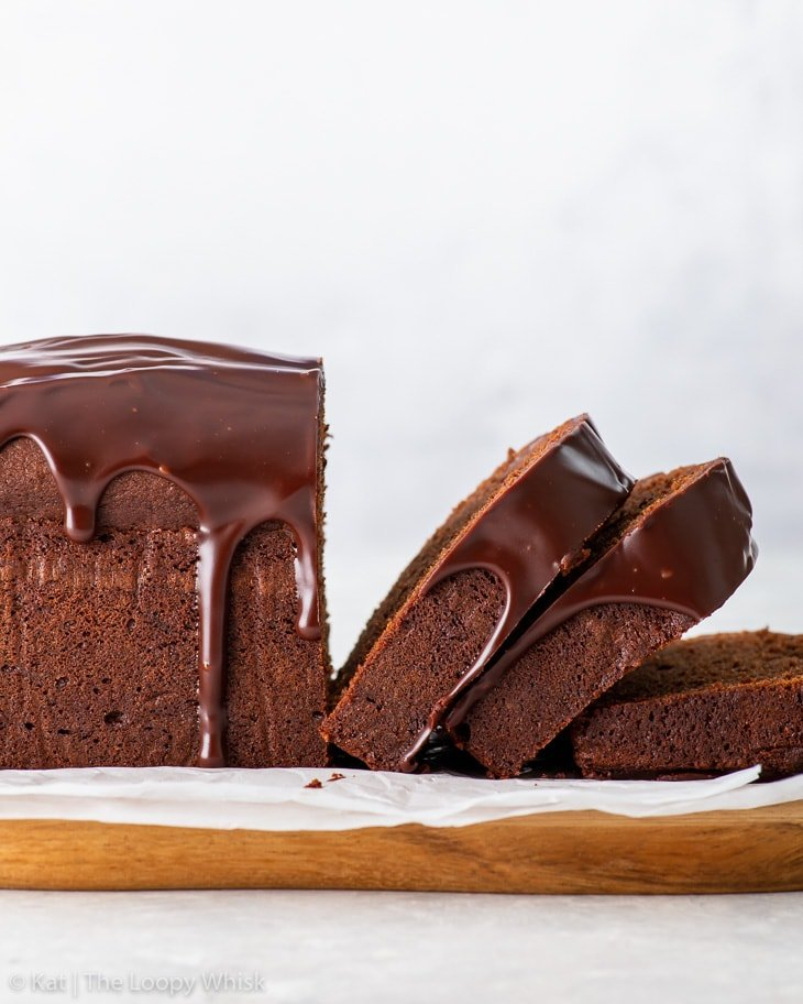 Side-on view of the partially sliced chocolate loaf cake on a piece of white parchment paper.