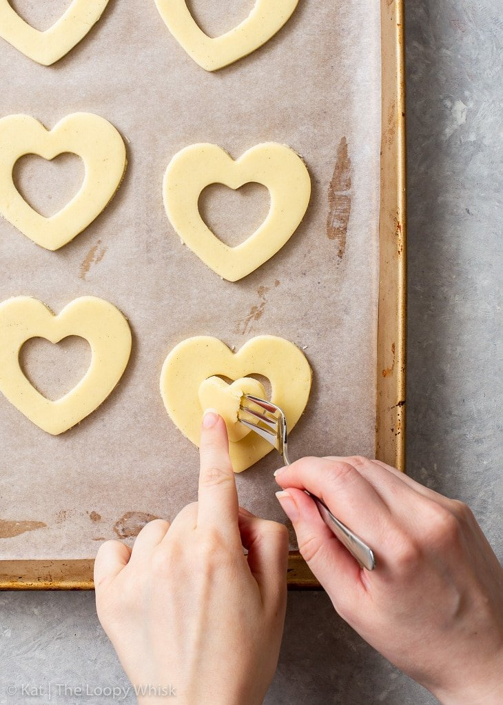 The process of cutting out and removing the middle of each heart-shaped shortbread cookie.