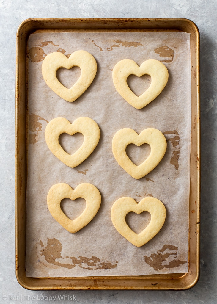 Baked heart-shaped shortbread cookies on a lined baking sheet.