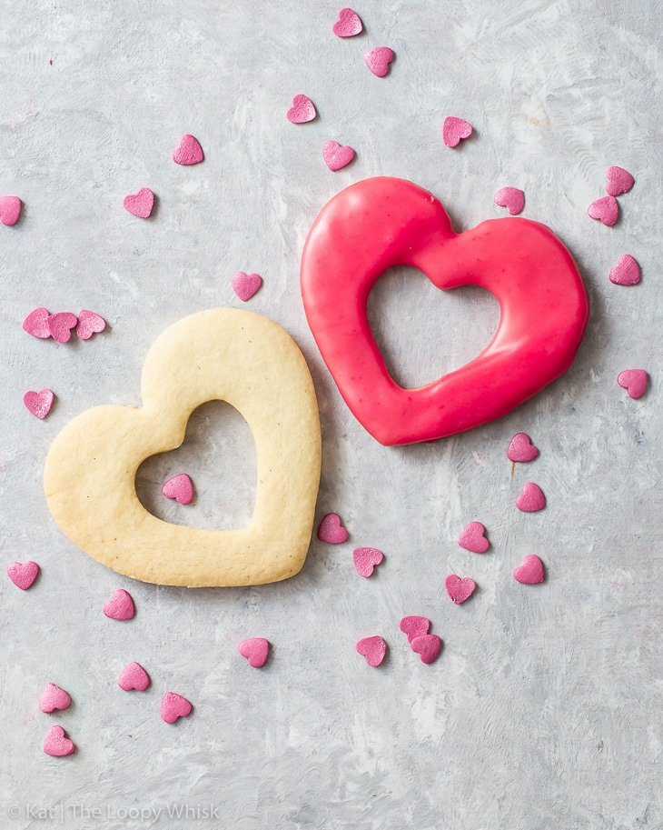 Two shortbread cookies: one plain without icing, the other decorated with pink raspberry icing.