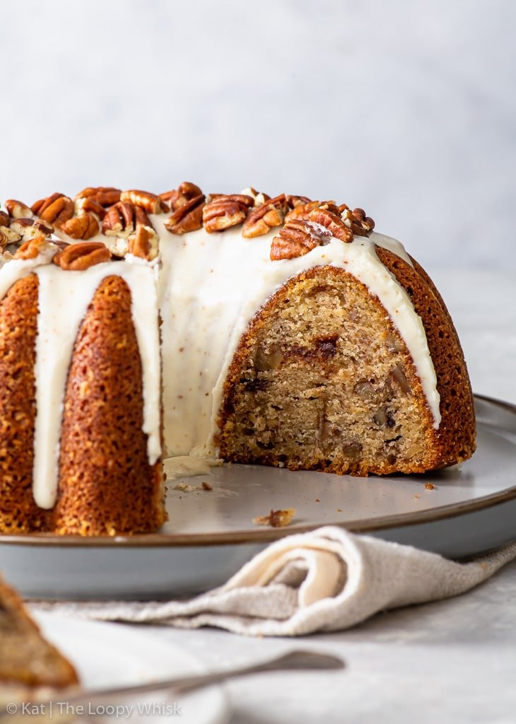 Banana bundt cake on a large dessert plate, with a few pieces cut from it.