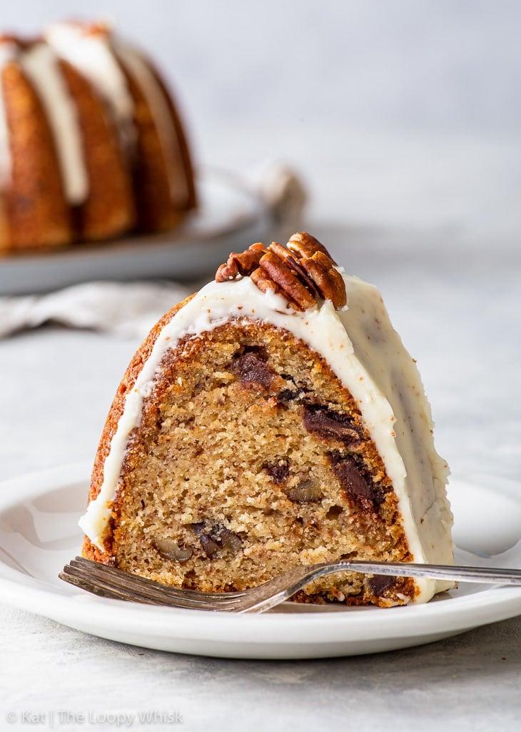A slice of banana bundt cake on a small white dessert plate.