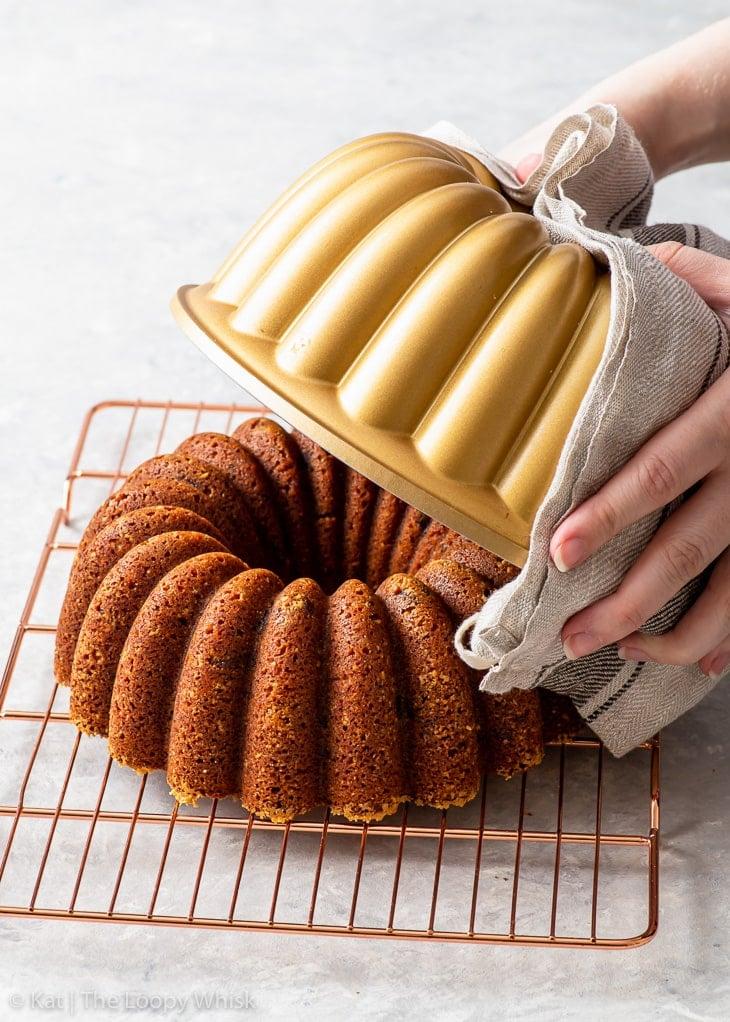 Removing the banana bundt cake from the bundt pan.