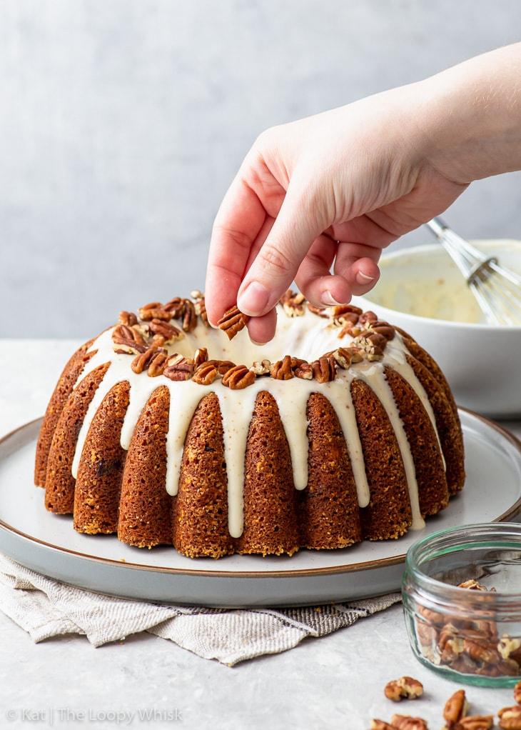 Decorating the iced banana bundt cake with chopped pecans.