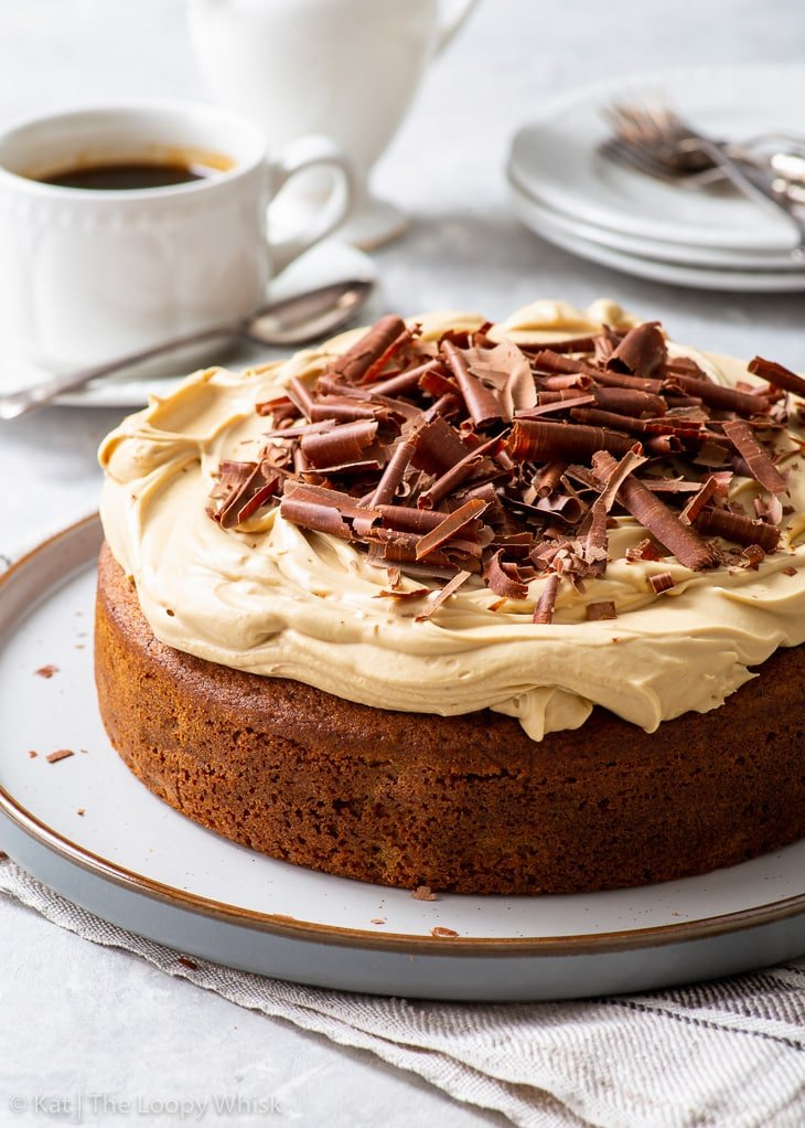 Coffee cake with cappuccino frosting on a large round dessert plate.