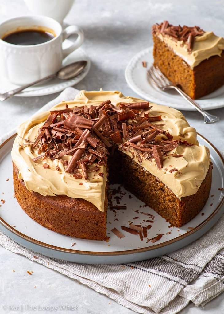 Coffee cake with cappuccino frosting on a large round dessert plate, with a few slices already cut.
