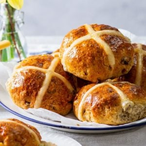 Gluten free hot cross buns on a large plate with a bunch of daffodils in the background.