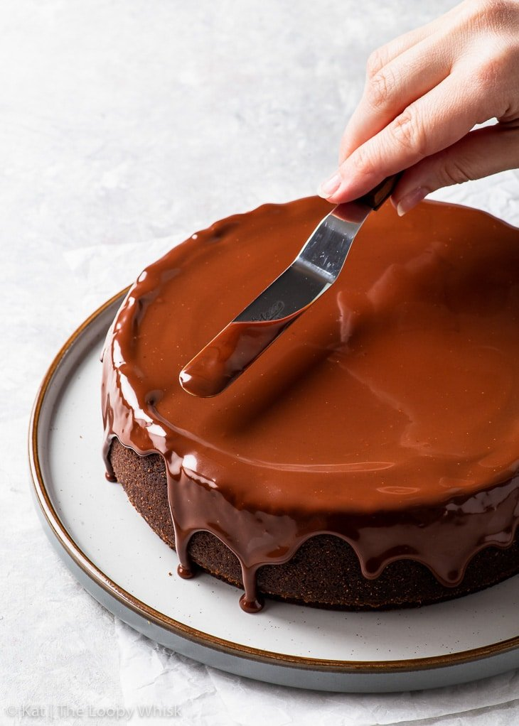 Spreading the ganache glaze on top of the cheesecake with a small offset spatula.