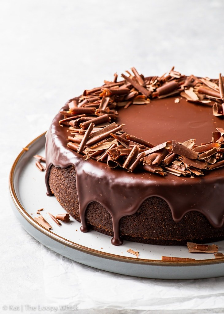 Triple chocolate cheesecake, decorated with glossy chocolate ganache and chocolate shavings, on a large dessert platter.