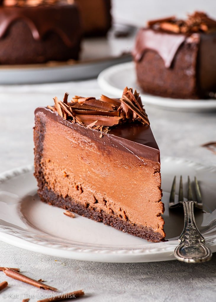 A slice of the triple chocolate cheesecake on a white dessert plate.