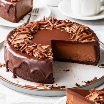 Triple chocolate cheesecake on a large dessert platter with a few slices already cut.