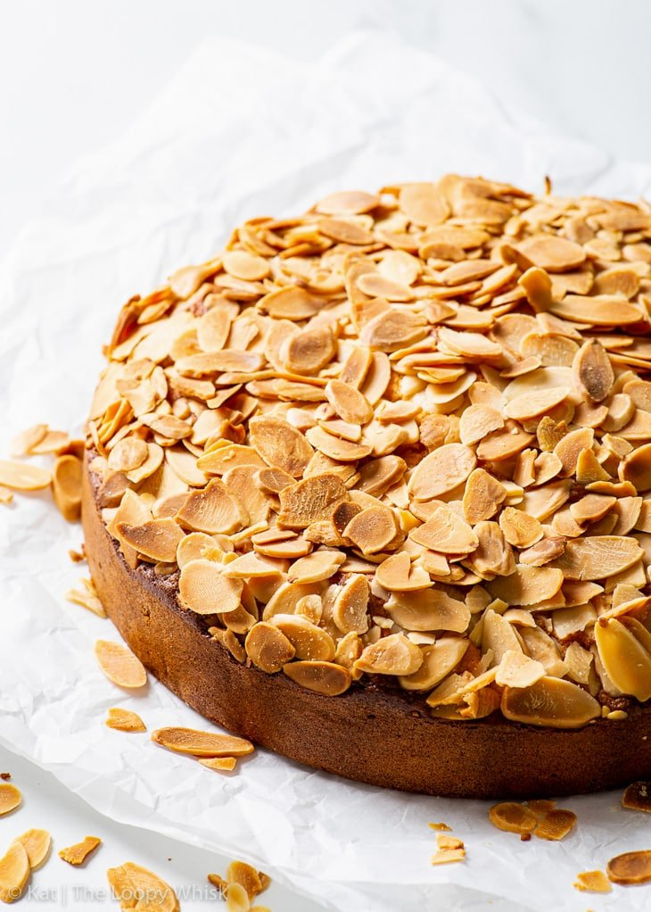 Gluten free almond cake on a piece of white parchment paper.