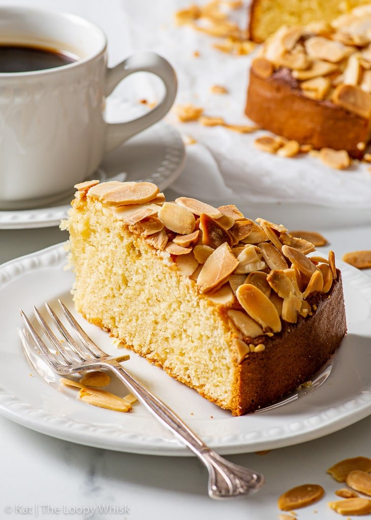 A piece of almond cake, topped with flaked almonds, on a white dessert plate.