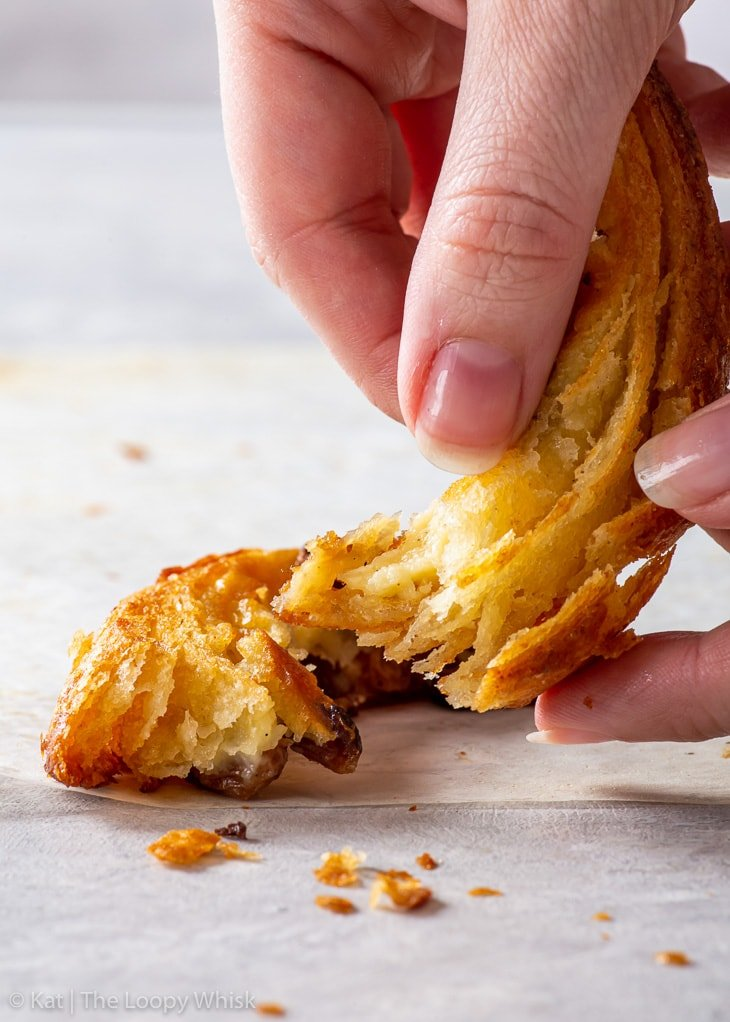 A hand holding a piece of gluten free Danish pastry, showing how flaky it is.