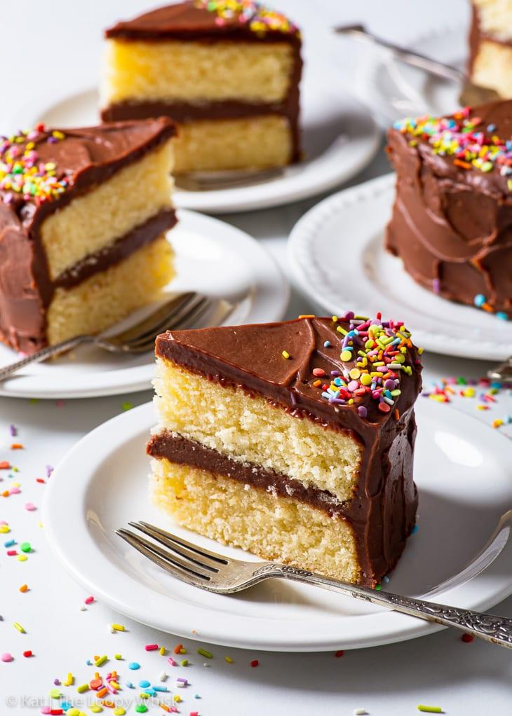 Slices of gluten free birthday cake on white dessert plates.
