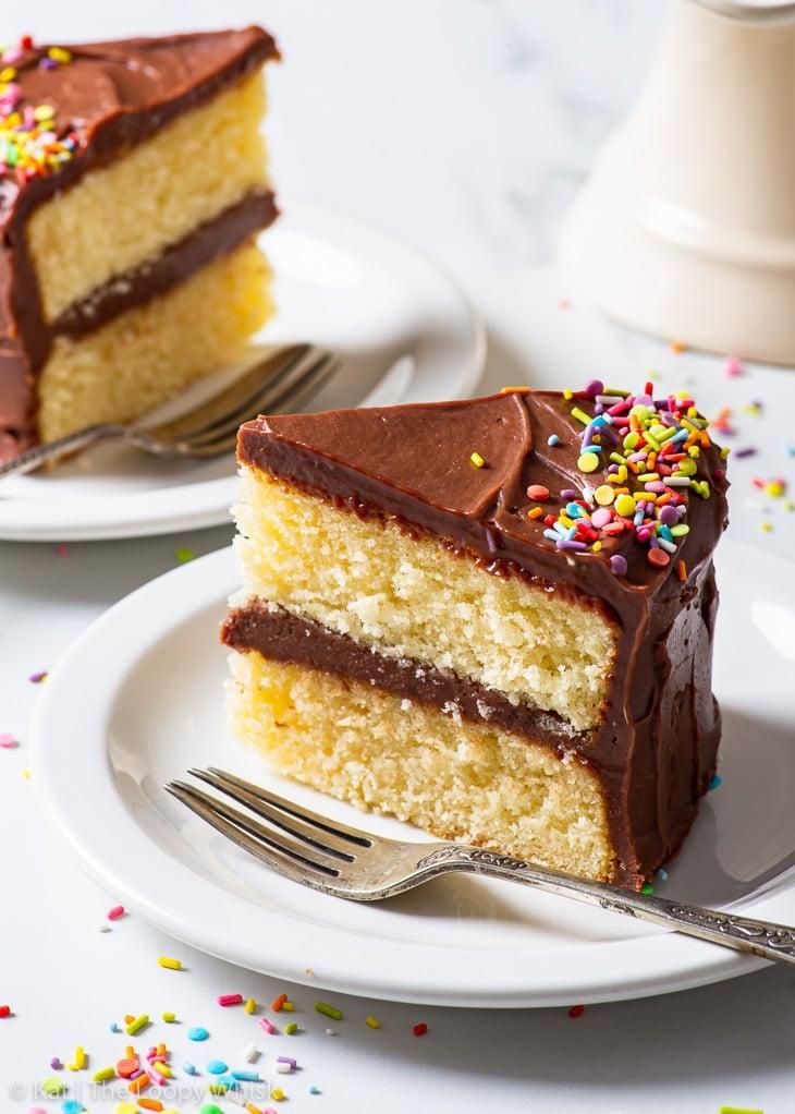 Two slices of gluten free birthday cake on white dessert plates.