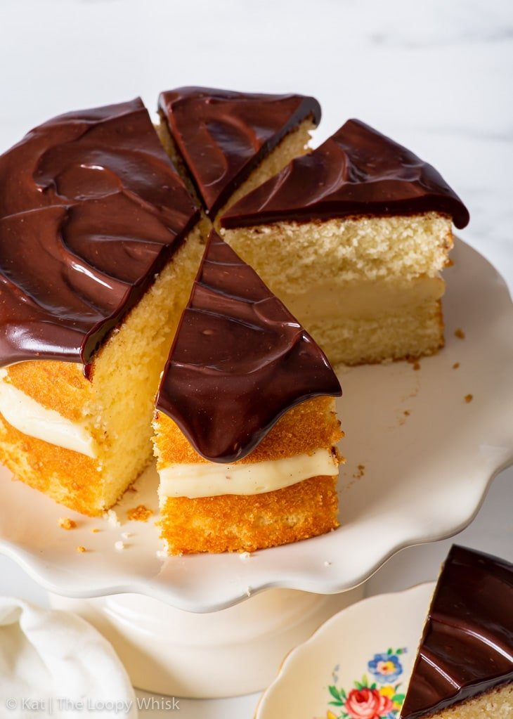 Small batch gluten free Boston cream pie on a white cake stand, with a few slices already cut.