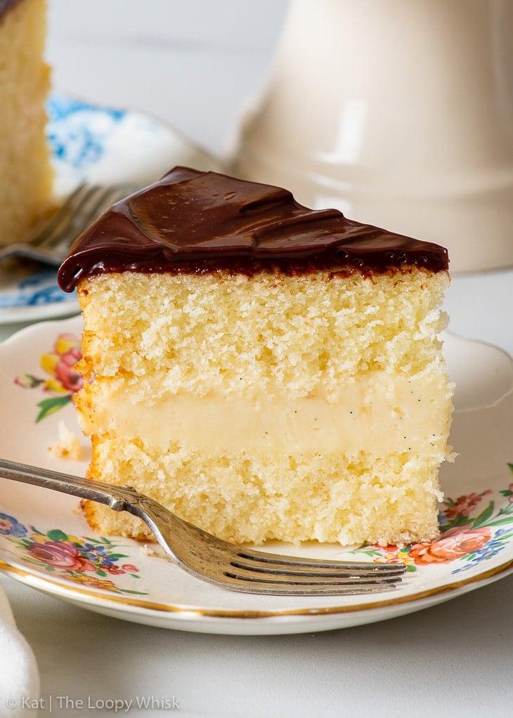 A slice of gluten free Boston cream pie on a small dessert plate.