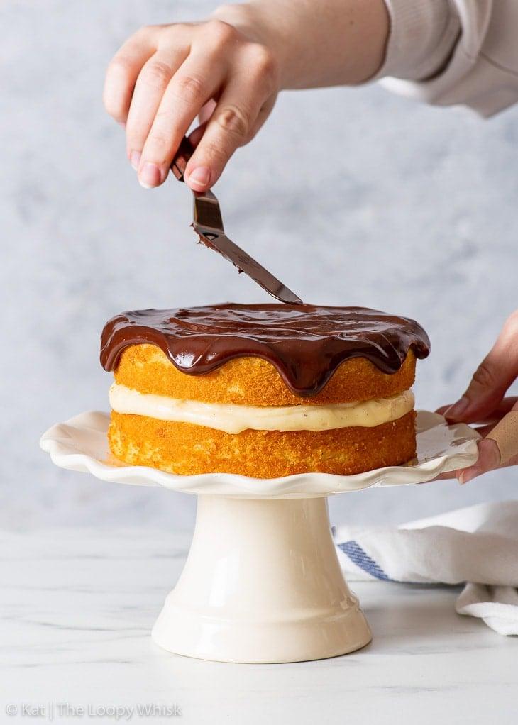 Decorating the top of the gluten free Boston cream pie with chocolate ganache.