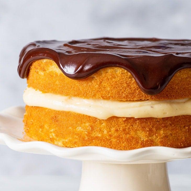 Small batch gluten free Boston cream pie on a white cake stand.
