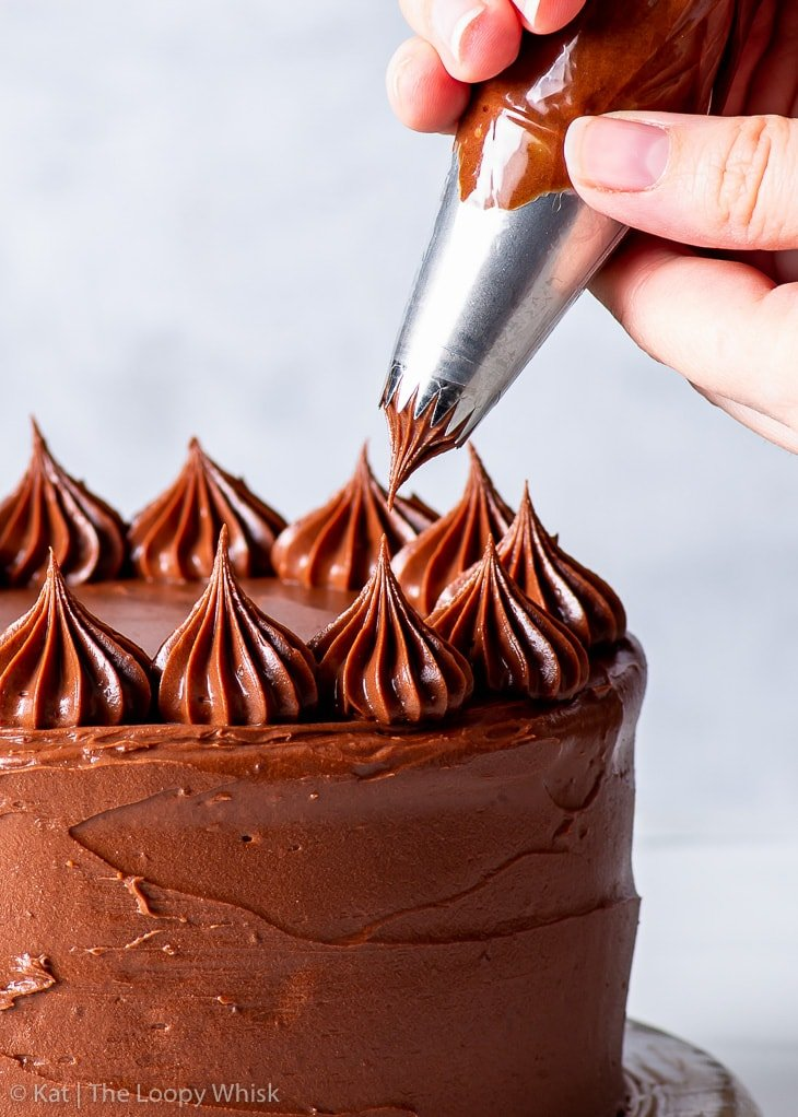 Piping swirls of chocolate frosting on top of the cake.