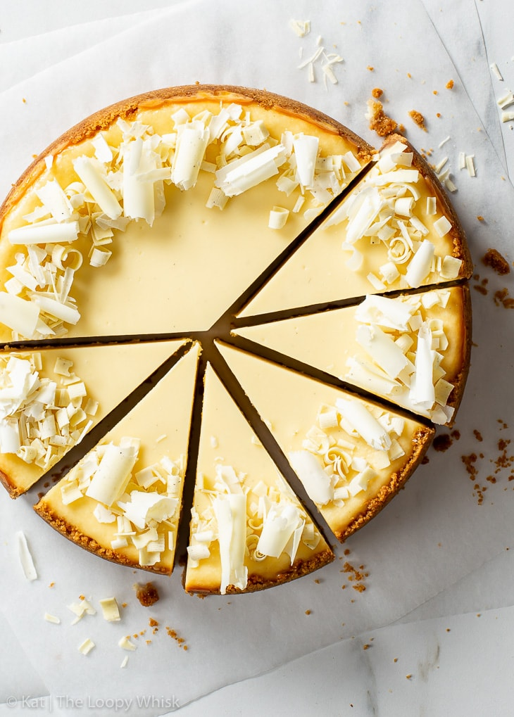 Overhead view of white chocolate cheesecake, cut into individual slices, on a sheet of white parchment paper.