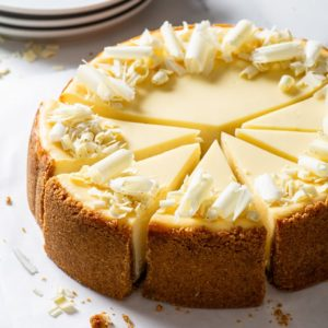 White chocolate cheesecake, cut into individual slices, on a sheet of white parchment paper.