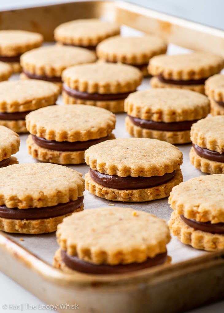 Hazelnut shortbread sandwich cookies with a ganache centre on a large baking sheet lined with white parchment paper.