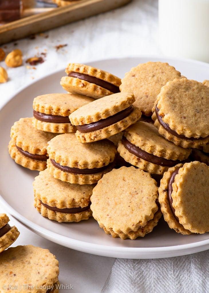 Hazelnut sandwich cookies on a white plate.