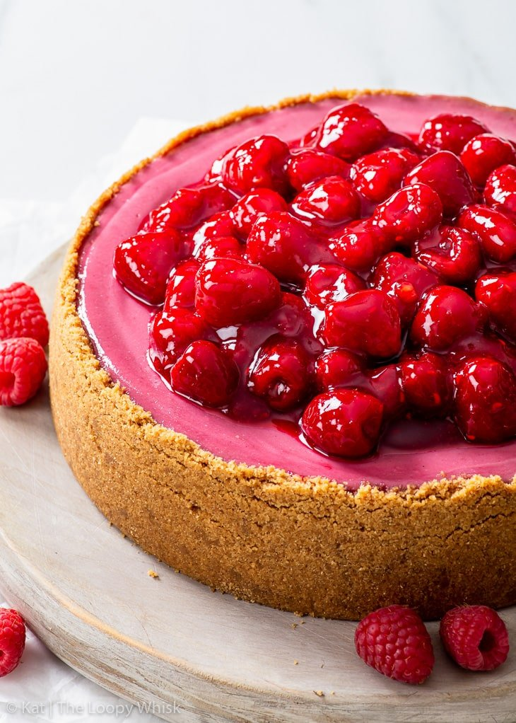 Raspberry cheesecake, topped with the raspberry sauce, on a large round wooden serving board.
