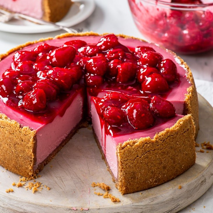 Raspberry cheesecake, topped with the raspberry sauce, on a large round wooden serving board, with a few slices already cut.