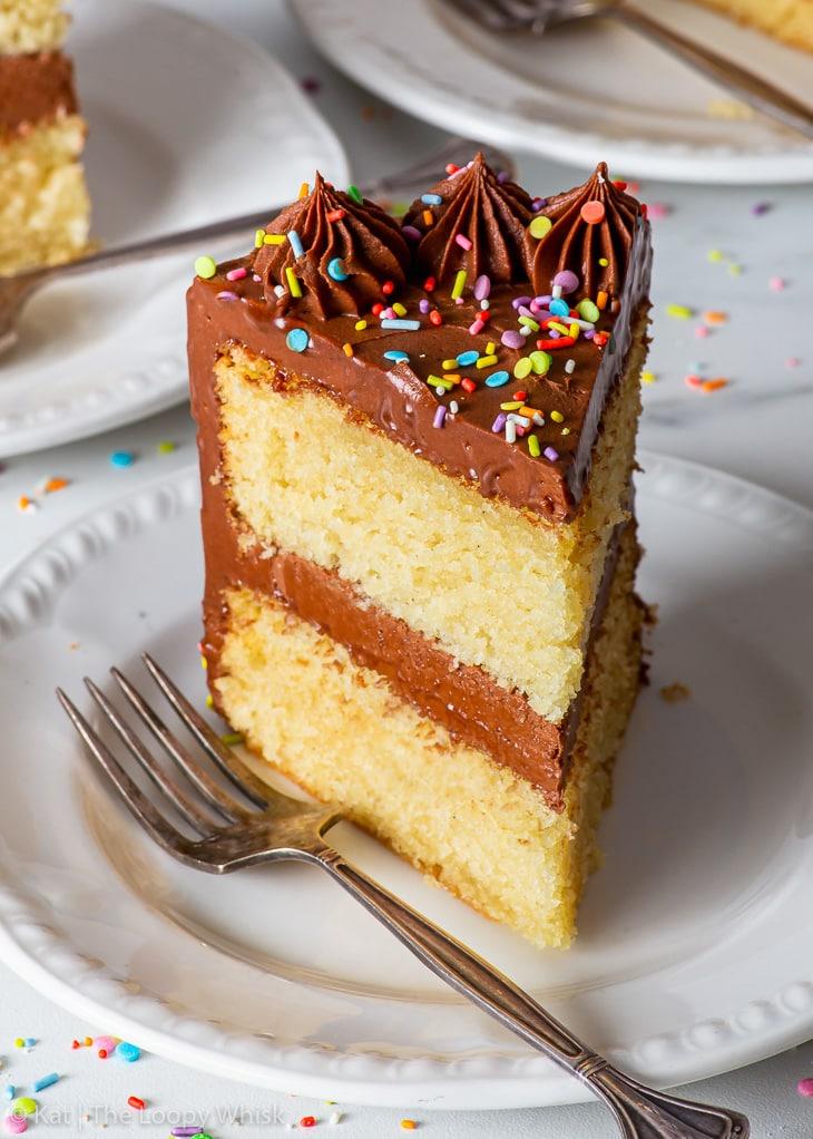 A slice of vegan birthday cake on a white dessert plate.