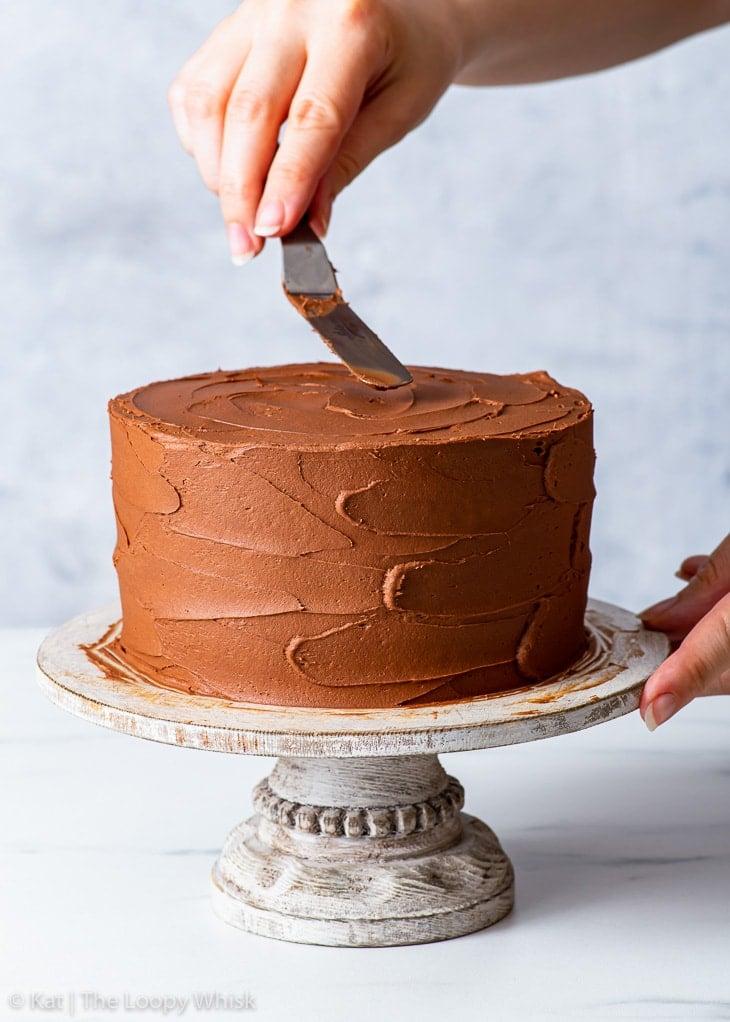 Spreading the whipped ganache frosting onto the vegan birthday cake.