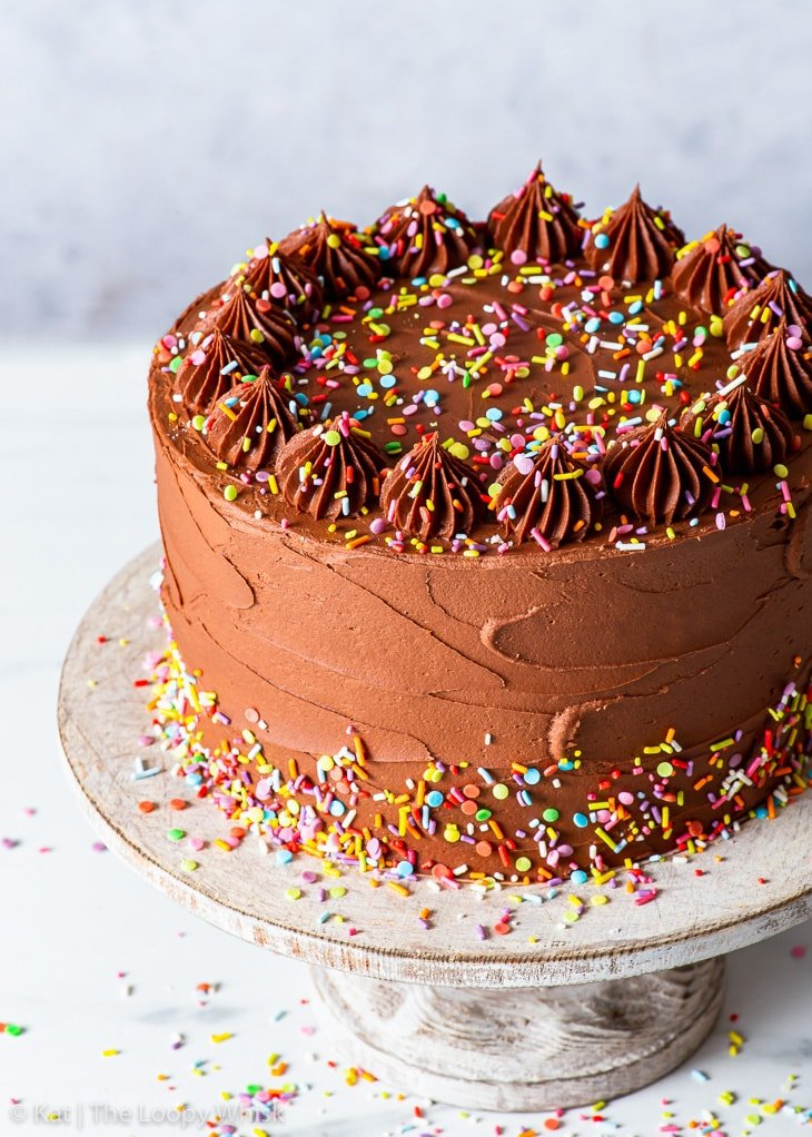 Vegan birthday cake decorated with sprinkles on a wooden cake stand.