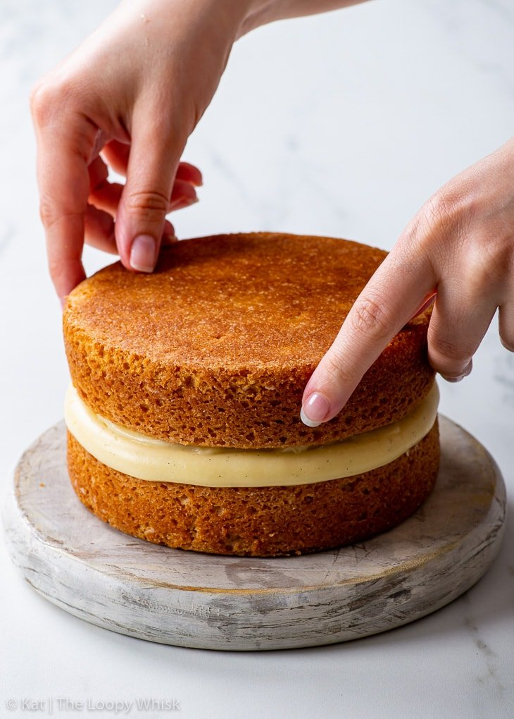 Placing the second sponge on top of the pastry cream layer.