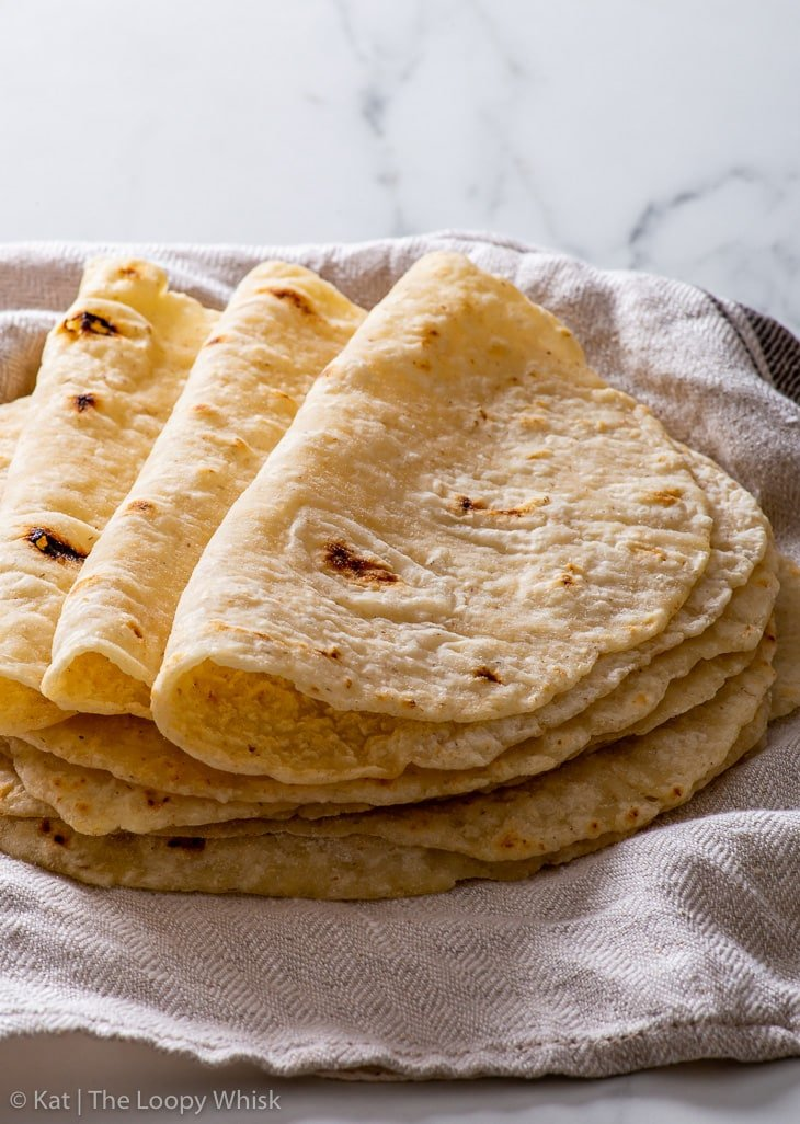 A stack of gluten free flour tortillas on a dish towel, with the top three ones folded over.
