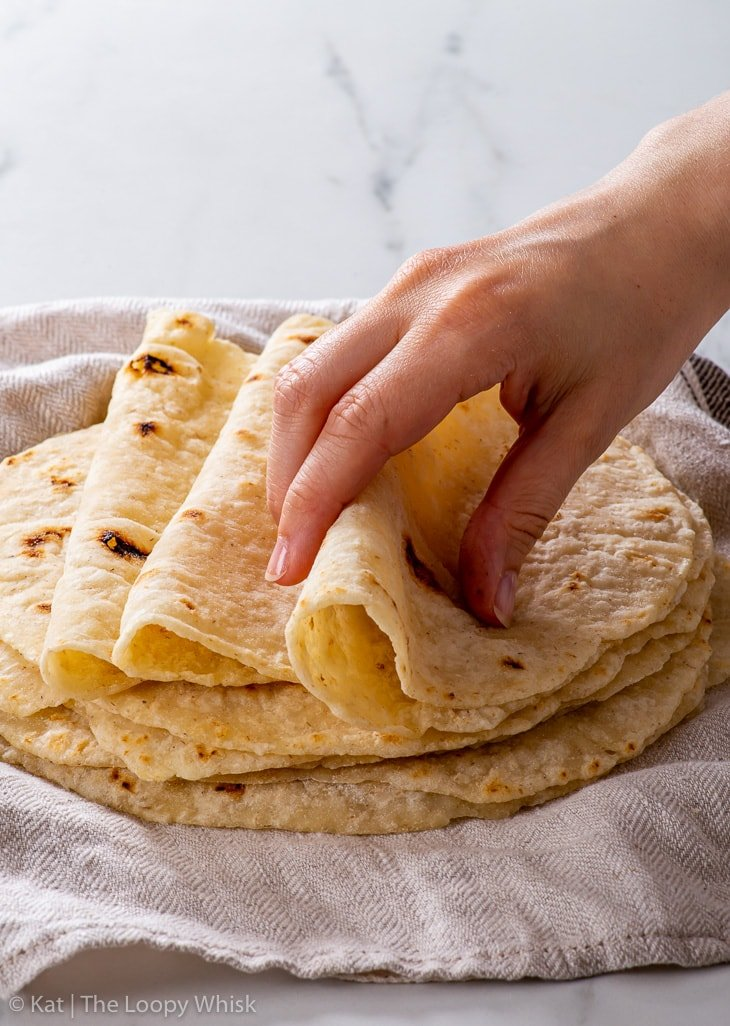 A hand taking hold of one gluten free flour tortilla.