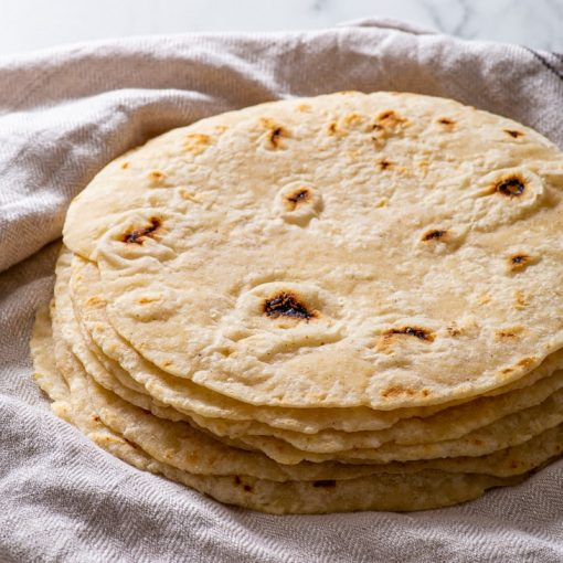 A stack of gluten free flour tortillas on a dish towel.