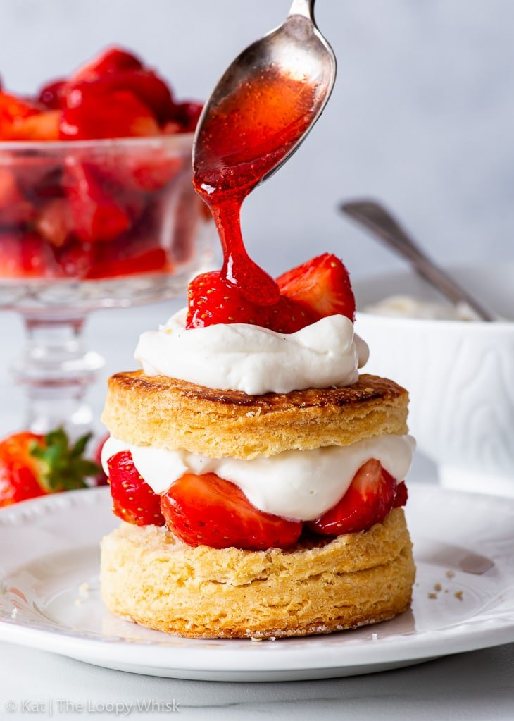 Gluten free strawberry shortcake on a white dessert plate, being drizzled with strawberry syrup.