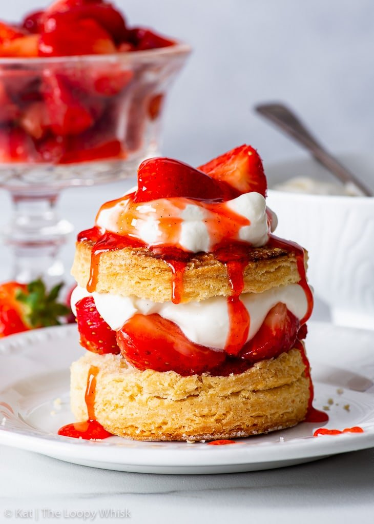 Gluten free strawberry shortcake on a white dessert plate, drizzled with strawberry syrup.