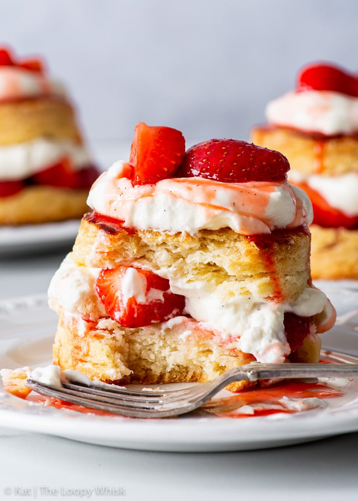 Gluten free strawberry shortcake on a white dessert plate, with a bite taken out of it.