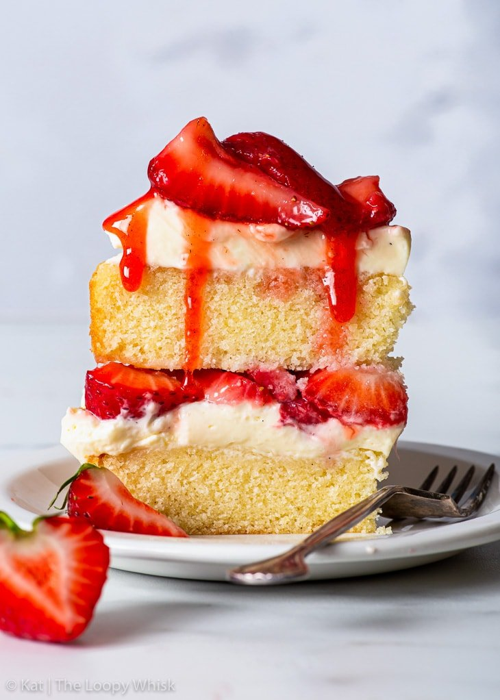A slice of gluten free strawberry shortcake cake on a white dessert plate.
