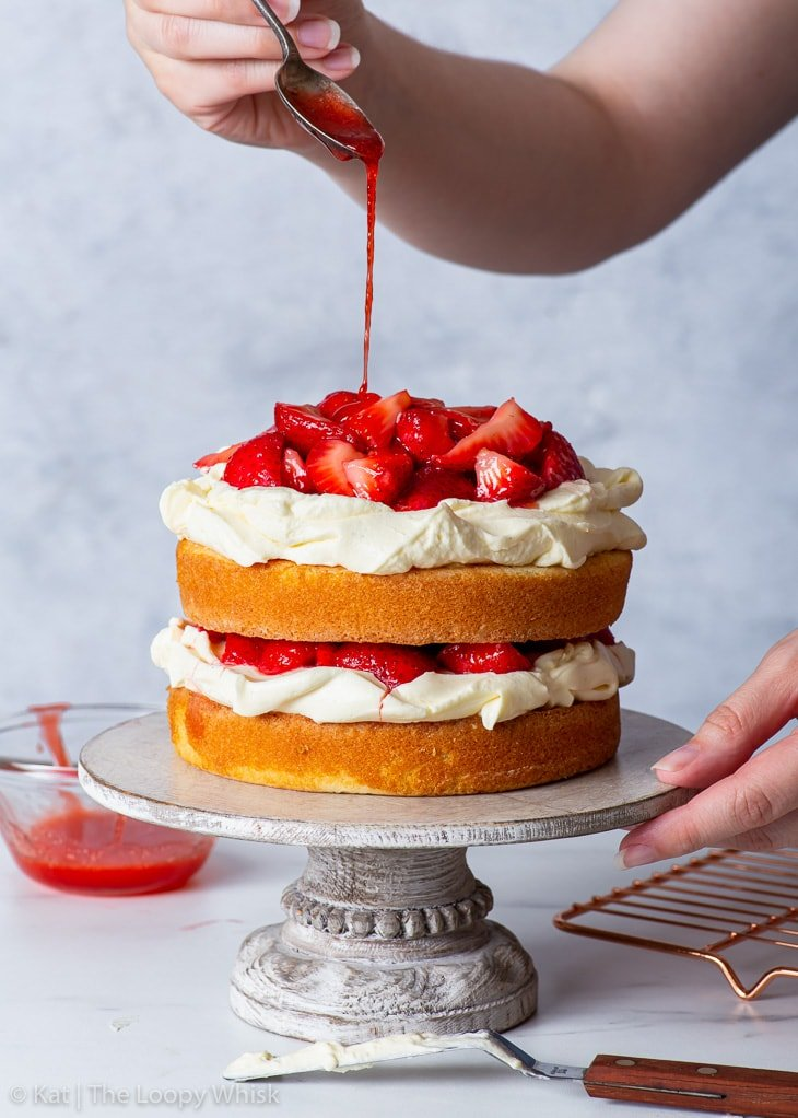 Drizzling the strawberry shortcake cake with strawberry syrup.